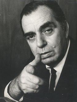 Foto de Nelson Rodrigues apontando o dedo indicador direito para a câmera. Em preto e branco, o autor tem olhos mortiços e uma verruga à esquerda da boca.