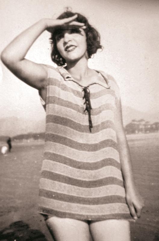Patrícia Galvão, a Pagu, na praia, cobrindo os olhos com a mão direita para fugir do sol. Cabelos curtos e sorriso, boca com batom. Está com camiseta grande listrada cobrindo apenas a parte de cima das pernas.