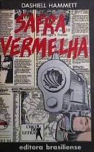 Capa do livro Safra Vermelha, indicando o autor Dashiell Hammett. Imagem com uma arma em primeiro plano e imagens de p[aginas de jornal ao fundo.