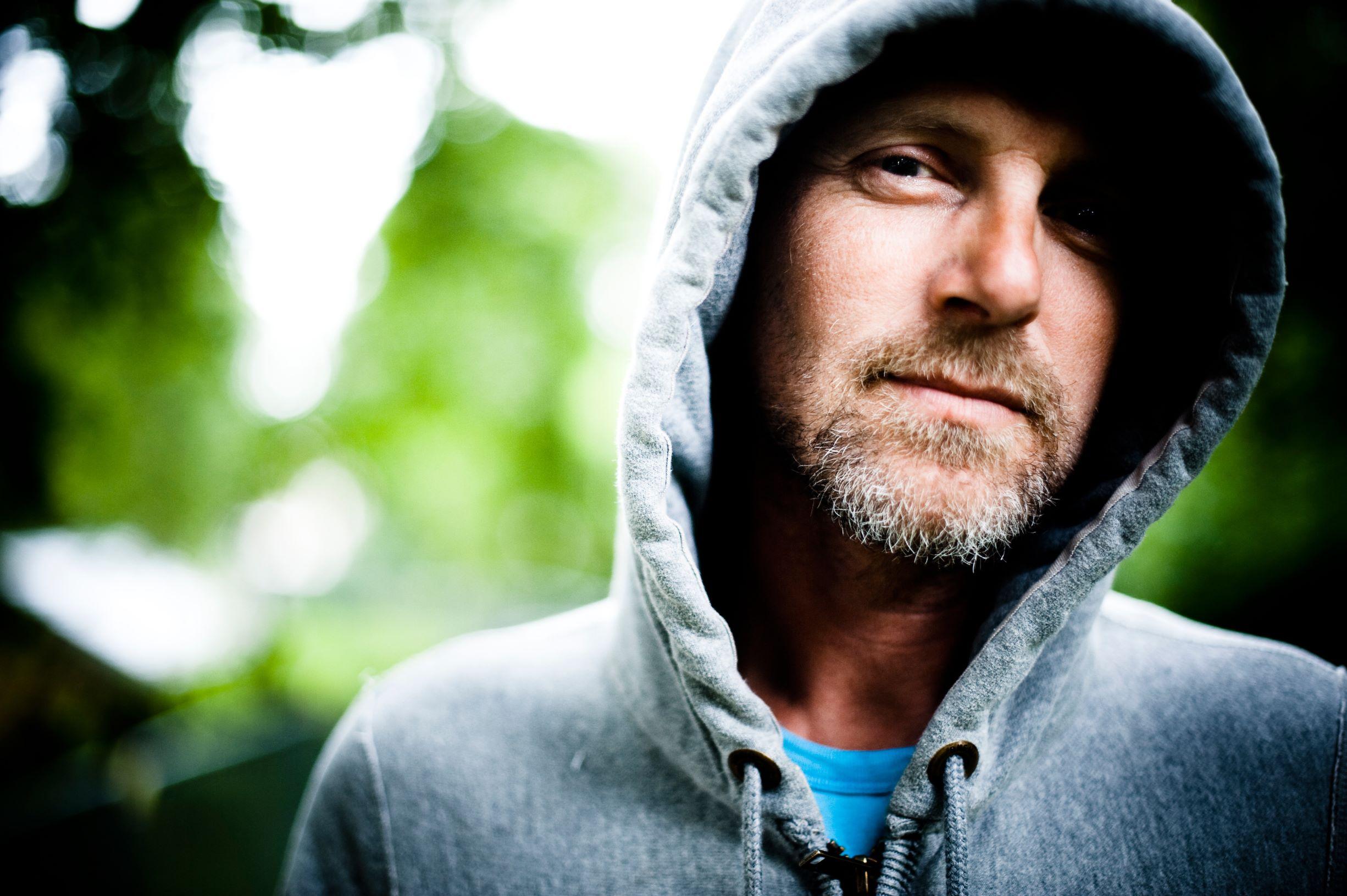 O escritor Jo Nesbo com capuz e camiseta azul, bigode e cavanhaque ao lado esquerdo da foto.