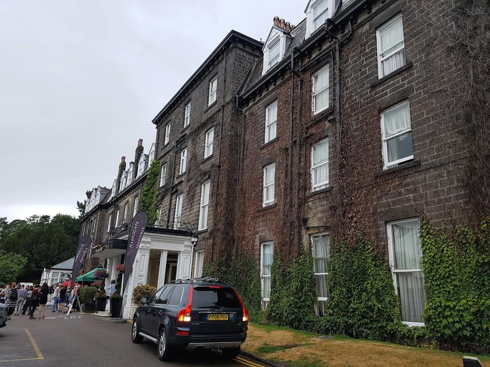 Foto mostra a fachada do Old Swan Hotel em Harrogate, Inglaterra. Ao fundo algumas pessoas e em primeiro plano um carro estacionado