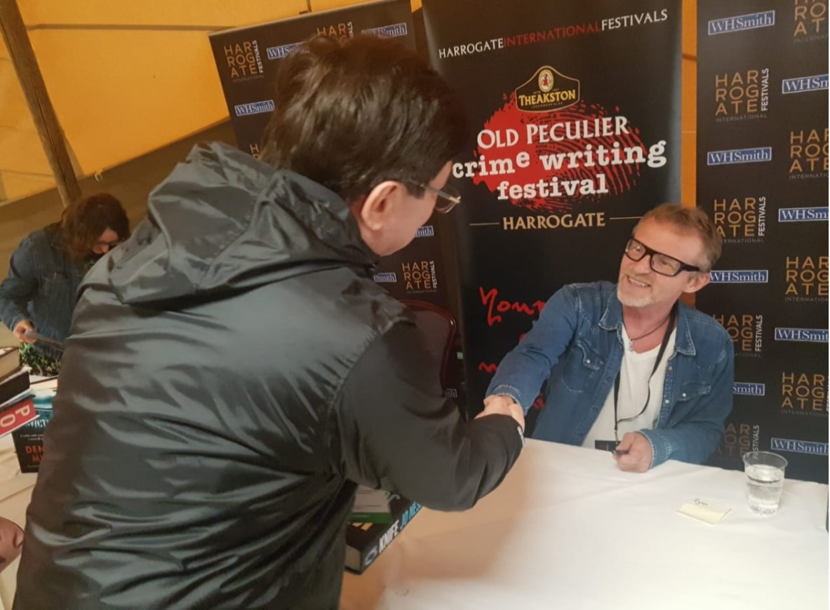 Escritor Jo Nesbo sentando, de óculos e cavanhaque branco, cumprimenta Pedro Cadina, que veste capa preta e está em pé de costas para câmera. Ao fundo, cartaz do Old Peculier Crime Writing Festival.