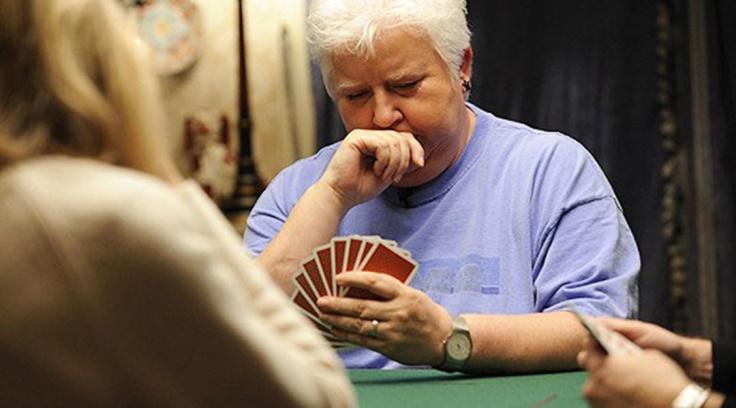 Iamgem da escritora Val McDermid em mesa de jogo de cartas. Com amão esquerda ela segura algumas cartas, a mão direita fechada está na boa. O ar é de reflexão.