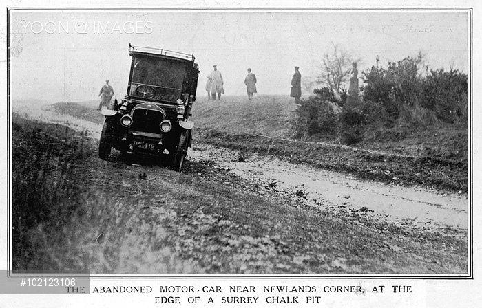 Imagem em preto e branco que mostra um carro Morris Cowley abandonado e atravessado entre a estrada e o canteiro. Atrás, alguns homens com capas de frio e chapéu.