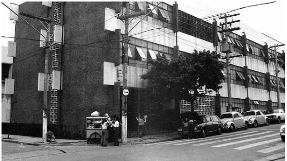 Fachada da Escola Estadual Bonifácio de Carvalho. Imagem em branco e preto da esquina, com carros estacionado à frente e um pipoqueiro atendendo uma criança.