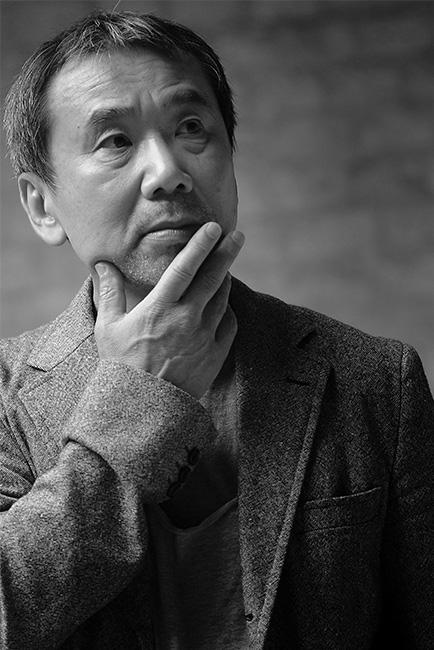 Foto em preto de branco do autor Harumi Murakami, olhando para o ceu e com a mão esquerda no queixo.