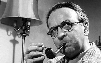 Raymond Chandler em foto preto e branco acendendo seu cachimbo.
