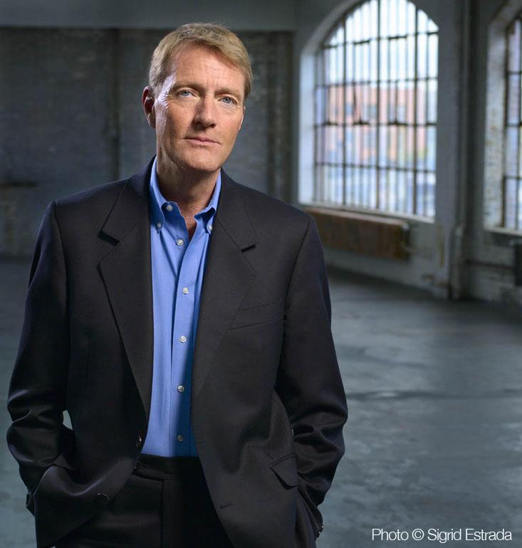 Lee Child de blazer e camisa azul olhando para a câmera à frente de uma grande janela.
